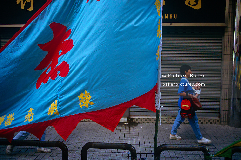 A Macanese mother carries her baby in a sling on her chest, passing a colourful banner on a Macau street, China.