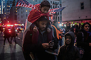 Man with his sons festooned with American flags at the Anti-Trump rally in Lower Manhattan, after the Trump administration implemented a ban on entry to citizens of 7 Muslim-majority nations into the United States.  New York, New York, USA.  29 January 2017