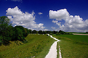A glorious, deep blue sky and lush green grass provide the perfect contrast to the brilliant white chalk path which undulates along the top of the raised bank surrounding the outer stone circle at Avebury, Wiltshire. Note how the shapes of the cumulus cloud masses mirror the angles of the chalk path perfectly.<br />