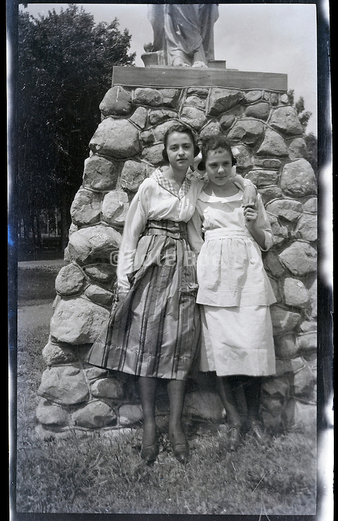 two young women posing by a monument 1920s