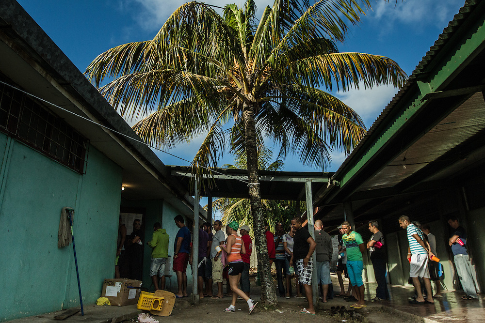 LA CRUZ, COSTA RICA - JANUARY 6, 2016: Cuban migrants wait in line for breakfast at a temporary migrant shelter at a local school near the Costa Rica/Nicaragua border. Nearly 8,000 migrants have been living in shelters in this tiny border town since early November, when Nicaraguan migration authorities denied them entry into their country, as the migrants travelled north with plans of arriving in the United States to take advantage of the1966 Cuban Adjustment Act, which allows Cubans who flee the island to enter the United States and apply for legal residency a year later. Many Cubans fear that this law will be revoked soon, because President Obama restored U.S. diplomatic relations Cuba. The latest wave of Cuban migration is also the result of a number of reforms made on the island that made it possible for homeowners to sell their properties, a move that triggered an exodus, because many more people could gather the funds to pay smugglers. Cuba also allowed its citizens to obtain passports and travel freely. PHOTO: Meridith Kohut for The New York Times
