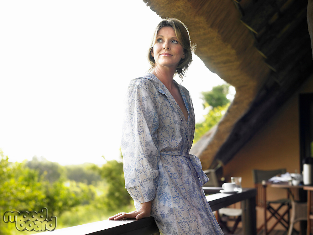 Portrait of adult woman on terrace in bathrobe looking over shoulder