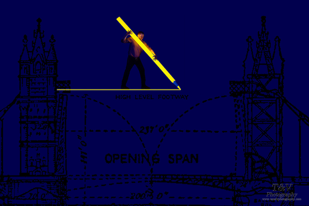 Man uses an oversized pencil to draw a foot path line on a blueprint of a draw bridge.Black light