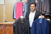 Portrait of man holding formal suits in menswear store