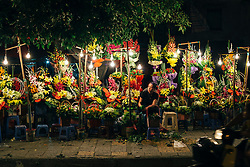 A vietnamese woman sits at night in front of her street flower stand, Hanoi, Vietnam, Southeast Asia