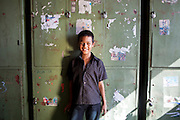 A young Nepalese boy smiles and laughs while he stands in the sunshine in front of green metal lockers in his bedroom in the Voice of Children rehabilitation center in Kathmandu, Nepal. The not-for-profit organisation supports street children and those who are at risk of sexual abuse through educational and vocational training opportunities, health services and psychosocial counseling.