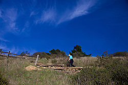 A woman hikes on a trail in Muir Woods National Monument, Marin County, California, United States of America