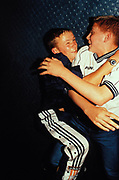Teenagers, wearing shirt and three-stripe shell suit trousers, wrestling, Ice Disco, UK 1997.