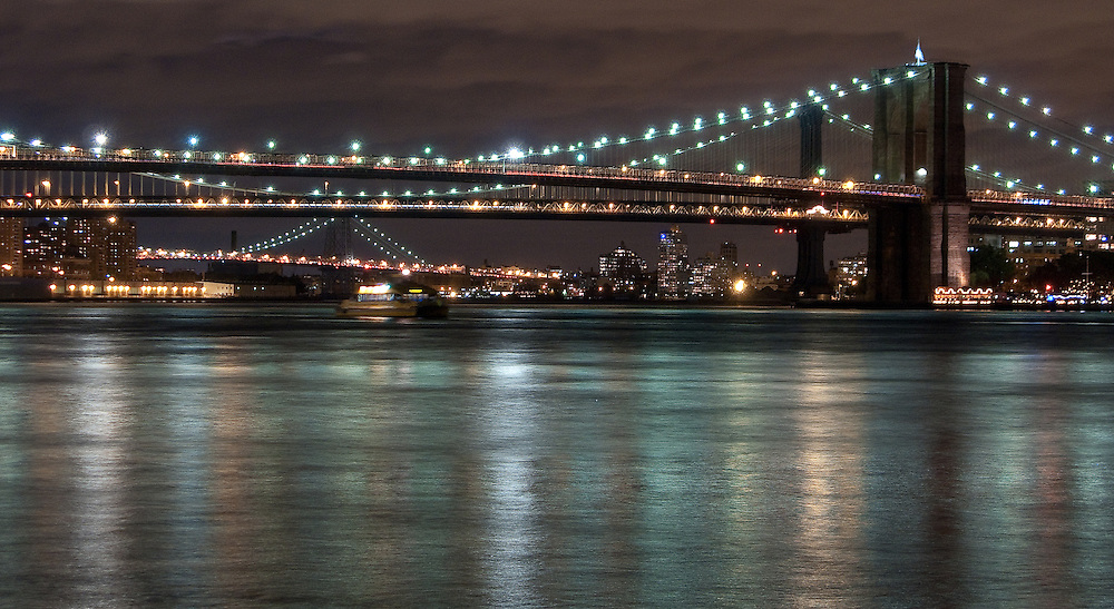 Brooklyn, Manhattan and Williamsburg bridges lit up at night shot from Pier 11 Ferry Terminal in Lower Manhattan