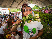 "15 JUNE 2014 - BANGKOK, THAILAND: A Thai woman waves white roses towards members of a police band during a ""Restore Happiness to Thais"" party in Lumpini Park in Bangkok. The Thai military junta, formally called the National Council for Peace and Order (NCPO), is sponsoring a series of events throughout Thailand to restore ""Happiness to Thais."" The events feature live music, dancing girls, military and police choirs, health screenings and free food.   PHOTO BY JACK KURTZ"