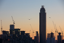 © Licensed to London News Pictures. 29/12/2016. London, UK. The sun sets behind construction cranes in central London after several days of freezing temperatures and intense fog in the capital. Photo credit: Rob Pinney/LNP