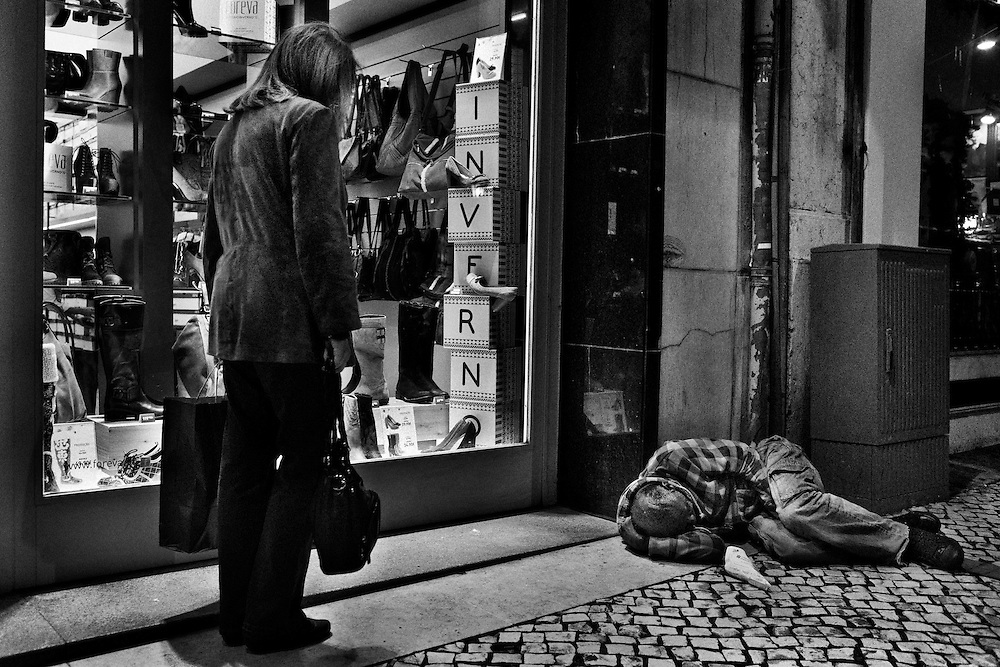 A homeless man sleeps by a shoes shop in Lisbon, Portugal, on November 10, 2012. Around 1.4 million people are currently unemployed in Portugal, and only 370,000 of them have receiving monthly social support from the government, leaving around 1 million people without the benefit. Over youths, unemployment rates is breaking records reaching 39% in the third quarter of the year, or equivalent to more than 175,000 people. The official unemployment rate in Portugal is currently on 15.7%, a bit away from the highest European rate in Spain, with 25.8%, followed by Greece with 25.1% of jobless. Photo by Mauricio Lima for The New York Times