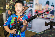 "11 JANUARY 2014 - BANGKOK, THAILAND:  A Thai boy plays with a M16 Assault Rifle during Children's Day in Bangkok. The Royal Thai Army hosted a ""Children's Day"" event at the 2nd Cavalry King's Guard Division base in Bangkok. Children had an opportunity to look at military weapons, climb around on tanks, artillery pieces and helicopters and look at battlefield medical facilities. The Children's Day fair comes amidst political strife and concerns of a possible coup in Thailand. Earlier in the week, the Thai army announced that movements of armored vehicles through Bangkok were not in preparation of a coup, but were moving equipment into position for Children's Day.     PHOTO BY JACK KURTZ"