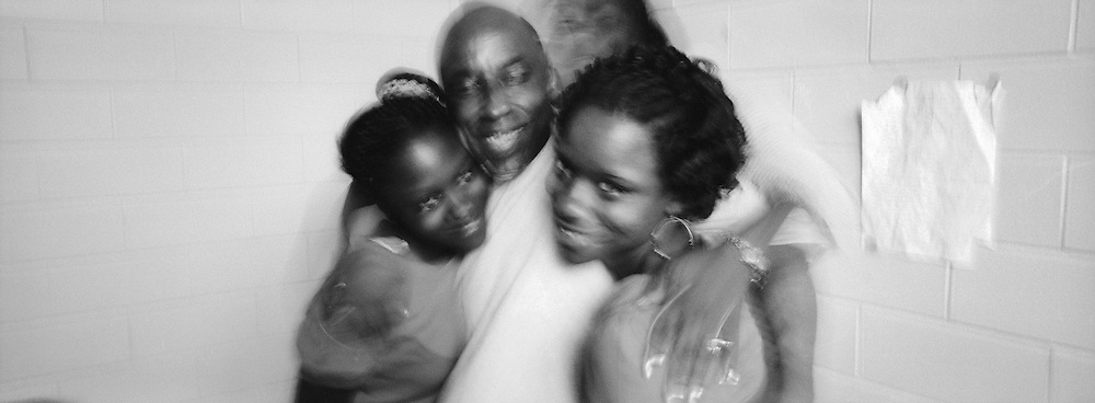 Van Morris, center, was reunited with his family through the Angola's prison hospice program. Hugging Morris are his two daughters Vanessa Zanders, 15, right, Charnese Zanders, 12, left, and Anitra Zanders, 32. Anitra is the girls' mother.