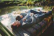Affectionate mid adult couple lying on pier by pond