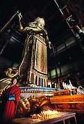 A freshly painted Buddha standing 26 meters tall in the Gandin Hid Monastery, Ulaanbaatar, Mongolia. It's full name is Gandantegchinlen; built in 1840, and one of the largest and most important in Mongolia. It was not destroyed in the religious purge of 1937 however. An agent of the Mongolia KGB was installed as head monk in 1980 where he stayed until religious freedom was granted in Mongolia in 1990. Mongols visit the monastery where a full complement of monks studies and worships.