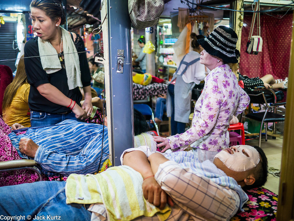 02 FEBRUARY 2013 - PHNOM PENH, CAMBODIA: A man gets a facial at a beauty parlor in a market in Phnom Penh, Cambodia.       PHOTO BY JACK KURTZ