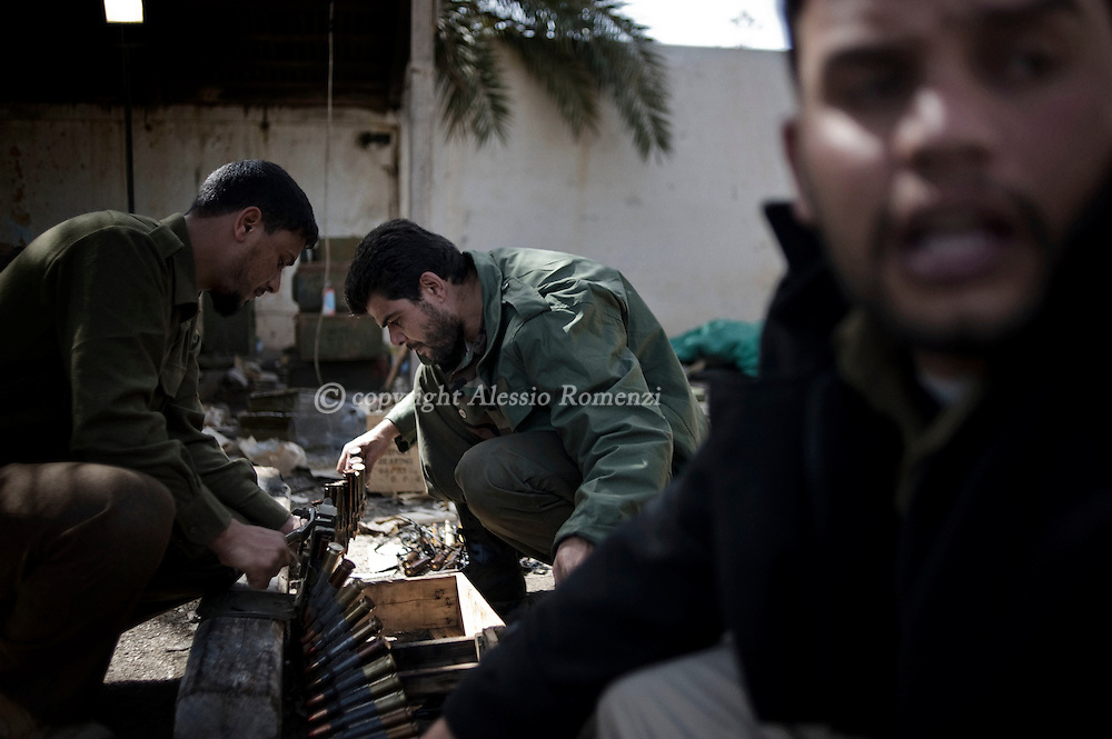 LIBYA, BENGHAZI. Libyan defected soldiers remove unspent bullets from a rusty cartridge belt of an anti-aircraft weapon at a military base in the eastern city of Benghazi on MarchALESSIO ROMENZI