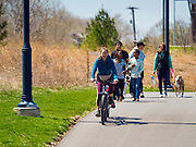 19 APRIL 2020 - DES MOINES, IOWA: People ride bikes and walk around Gray's Lake, a popular public park and lake south of downtown Des Moines. After a week of colder than normal weather, including three inches of snow, the weekend was spring like and people went to public parks to enjoy the pleasant weather.      PHOTO BY JACK KURTZ