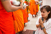 "22 JULY 2013 - PHRA PHUTTHABAT, THAILAND: A woman prays as monks past her during the Tak Bat Dok Mai at Wat Phra Phutthabat in Saraburi province of Thailand, Monday, July 22. Wat Phra Phutthabat is famous for the way it marks the beginning of Vassa, the three-month annual retreat observed by Theravada monks and nuns. The temple is highly revered in Thailand because it houses a footstep of the Buddha. On the first day of Vassa (or Buddhist Lent) people come to the temple to ""make merit"" and present the monks there with dancing lady ginger flowers, which only bloom in the weeks leading up Vassa. They also present monks with candles and wash their feet. During Vassa, monks and nuns remain inside monasteries and temple grounds, devoting their time to intensive meditation and study. Laypeople support the monastic sangha by bringing food, candles and other offerings to temples. Laypeople also often observe Vassa by giving up something, such as smoking or eating meat. For this reason, westerners sometimes call Vassa the ""Buddhist Lent.""     PHOTO BY JACK KURTZ"