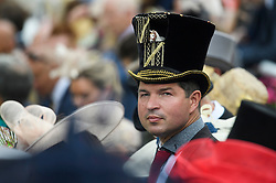 © Licensed to London News Pictures. 19/06/2018. London, UK.  A racegoers with a horse themed hat watches members of the Royal Family arrive at day one of Royal Ascot at Ascot racecourse in Berkshire, on June 19, 2018. The 5 day showcase event, which is one of the highlights of the racing calendar, has been held at the famous Berkshire course since 1711 and tradition is a hallmark of the meeting. Top hats and tails remain compulsory in parts of the course. Photo credit: Ben Cawthra/LNP