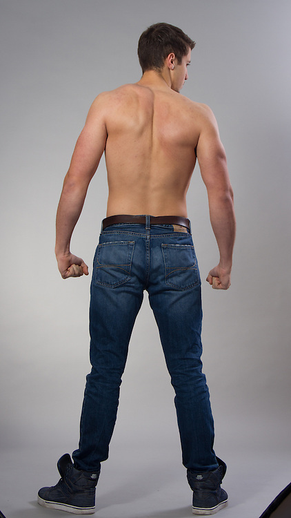 Male model posing in a contemporary outfit without a shirt.