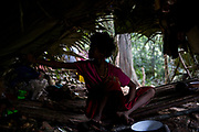 A Maniq girl sits inside her hut made of sticks and leaves.<br /> <br /> Evidence suggests that the Maniq, a Negrito tribe of hunters and gatherers, have inhabited the Malay Peninsula for around 25,000 years. Today a population of approximately 350 maniq remain, marooned on a forest covered mountain range in Southern Thailand. Whilst some have left their traditional life forming small villages, the majority still live the way they have for millennia, moving around the forest following food sources. <br /> <br /> Quiet and reclusive they are little known even in Thailand itself but due to rapid deforestation they are finding it harder to survive on the forest alone and are slowly being forced to move to its peripheries closer to Thai communities.