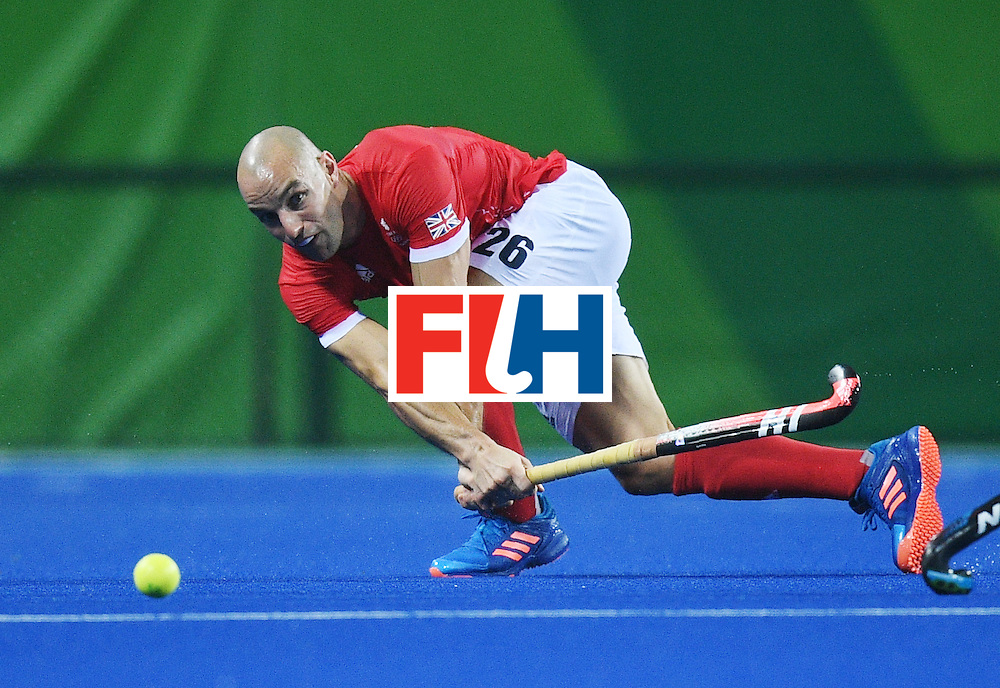 Britain's Nick Catlin hits the ball during the men's field hockey Britain vs New Zealand match of the Rio 2016 Olympics Games at the Olympic Hockey Centre in Rio de Janeiro on August, 7 2016. / AFP / MANAN VATSYAYANA        (Photo credit should read MANAN VATSYAYANA/AFP/Getty Images)