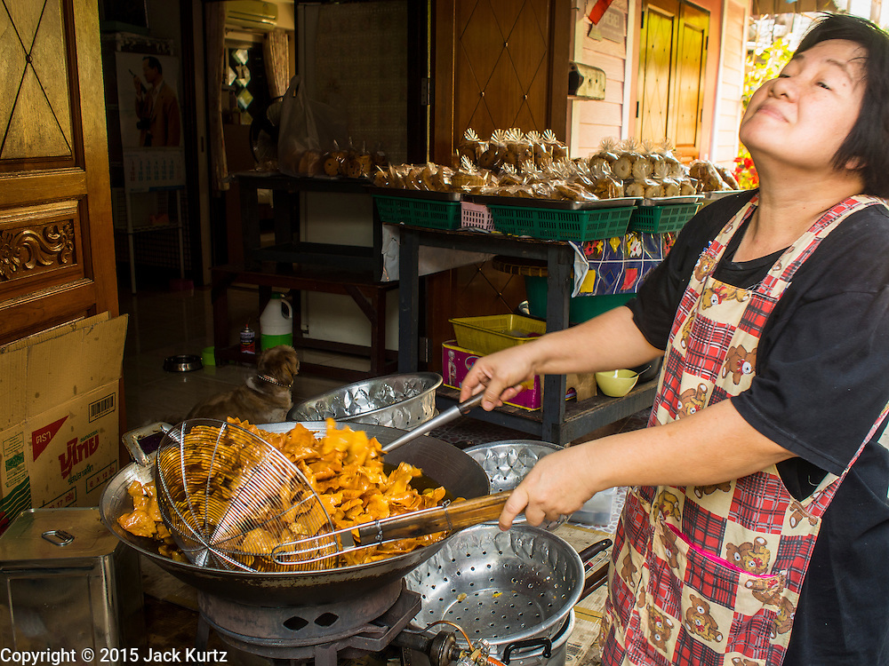 06 FEBRUARY 2015 - BANGKOK, THAILAND: A woman makes potato chips in her shop near Santa Cruz Church in the Thonburi section of Bangkok. Now the neighborhood around the church is known for the Thai adaptation of Portuguese cakes baked in the neighborhood. Several hundred Siamese (Thai) Buddhists converted to Catholicism in the 1770s. Some of the families started baking the cakes. When the Siamese Empire in Ayutthaya was sacked by the Burmese, the Portuguese and Thai Catholics fled to Thonburi, in what is now Bangkok. The Portuguese established a Catholic church near the new Siamese capital. There are still a large number of Thai Catholics living in the neighborhood around the church.       PHOTO BY JACK KURTZ