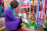 "15 JANUARY 2010 - TUCSON, AZ:    A woman prays at a memorial for the victims of the mass shooting in Tucson, AZ, Saturday, January 15, one week after the shooting. Six people were killed and 14 injured in the shooting spree at a ""Congress on Your Corner"" event hosted by Arizona Congresswoman Gabrielle Giffords at a Safeway grocery store in north Tucson on January 8. Congresswoman Giffords, the intended target of the attack, was shot in the head and seriously injured in the attack but is recovering. Doctors announced that they removed her breathing tube Saturday, one week after the attack. The alleged gunman, Jared Lee Loughner, was wrestled to the ground by bystanders when he stopped shooting to reload the Glock 19 semi-automatic pistol. Loughner is currently in federal custody at a medium security prison near Phoenix. PHOTO BY JACK KURTZ"