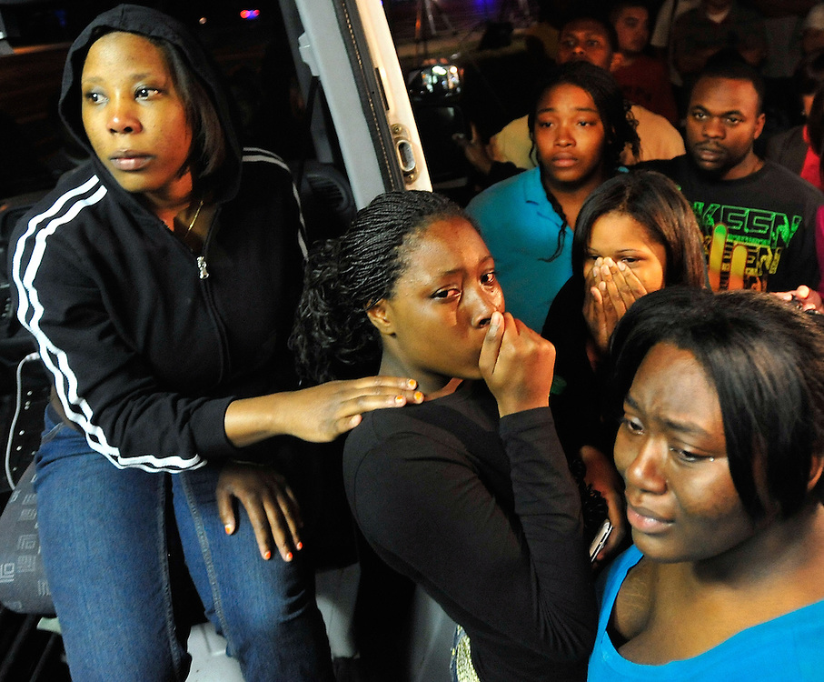 Family members, Balinda Hood, center, and Jennifer Hood, middle-right, are comforted by friends as they watch from the back of a news van as Jamie Hood surrenders to the police after a four day manhunt on Friday, March 25, 2011 in Athens, Ga.