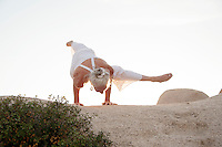 Seniro woman in yoga arm balance on stone landscape.