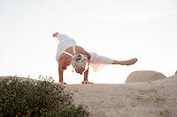 Seniro woman in yoga arm balance on stone landscape.
