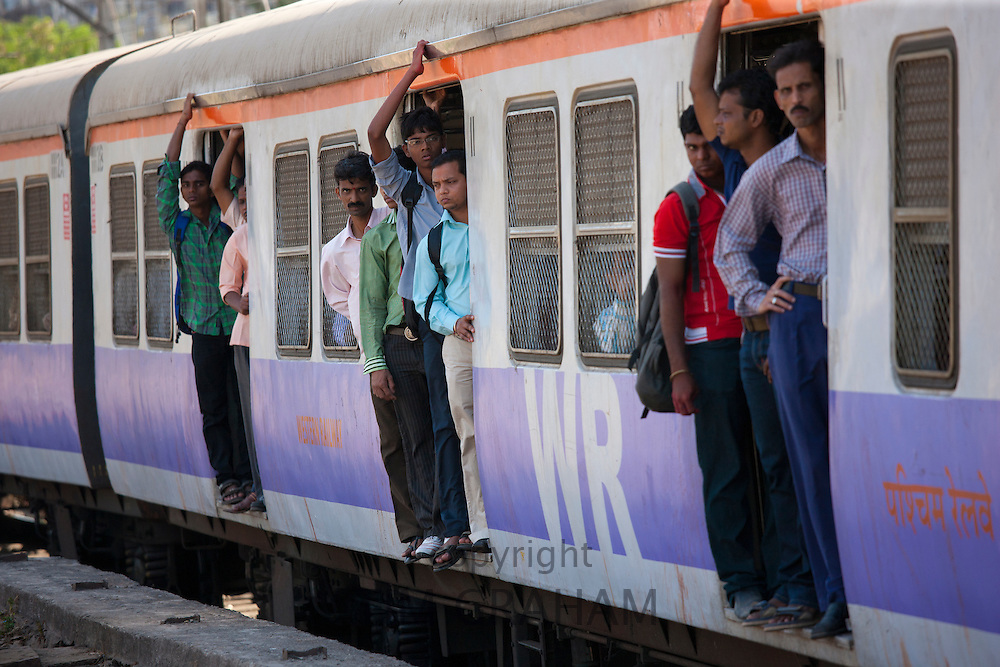 Office workers on crowded commuter train of Western Railway near Mahalaxmi Station on the Mumbai Suburban Railway, India