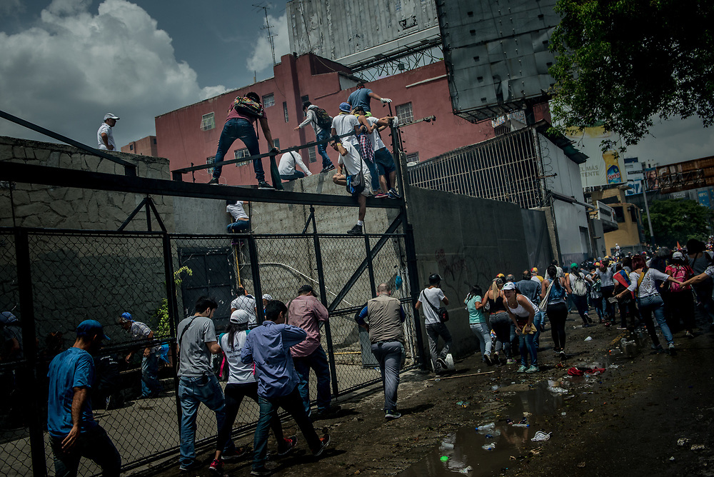 CARACAS, VENEZUELA - APRIL 19, 2017:  Overcome by tear gas raining down on them, and surrounded by riot police, opposition protesters started climbing up buildings and running across rooftops in order to flee authorities.  Thousands of protesters took to the streets today in Venezuela to protest their discontent with the government.  They were met by riot police that fired tear gas and rubber bullets at them.  Some protesters responded by throwing rocks and petrol bombs.  Venezuela is in crisis, and residents face daily struggles over food and medicine shortages, and one of the highest crime rates in the world.  PHOTO: Meridith Kohut