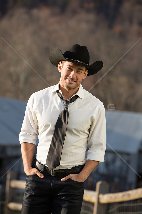 cowboy in a shirt and tie on a ranch