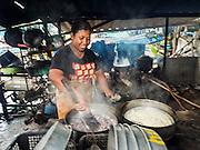15 JUNE 2105 - NARATHIWAT, NARATHIWAT, THAILAND:  A women cooks rice over wood fired stoves near the fishing port in Narathiwat.      PHOTO BY JACK KURTZ