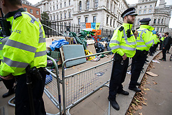 © Licensed to London News Pictures. 09/10/2019. London, UK. Police remove tents and equipment from an Extinction Rebellion roadblock on Horse Guards Road. Police continue to attempt to clear roads in Westminster on the third day of the protest.  Photo credit: George Cracknell Wright/LNP