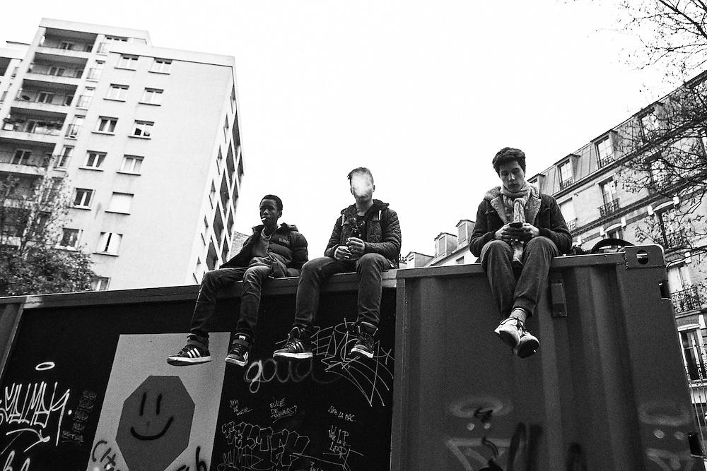 Des jeunes partagent un joint sur un conteneur installé sur les rails, non loin de Ménilmontant.