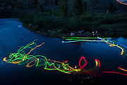 Noah Fraser, who organized this years world mystery championships squirt boats at night at the spot along the Truckee River near Reno, Nev., with glowsticks attached to his boat and paddle. This was a  concept shoot designed to show what squirt boats do under water ahead of the world mystery championships.