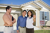 Young couple buying house, holding keys