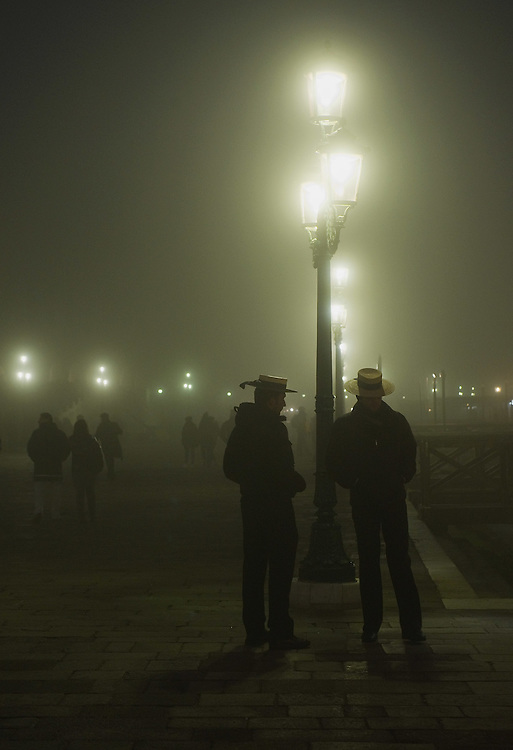 VENICE, ITALY - NOVEMBER 20:  Two gondoliers talks to each other in St Mark's Square as thick fog shrouds the city, on November 20, 2011 in Venice, Italy. Venice woke up this morning under a heavy blanket of fog adding to the atmosphere of the city.<br /> <br /> HOW TO LICENCE THIS PICTURE: please contact us via e-mail at sales@xianpix.com or call our offices London   +44 (0)207 1939846 for prices and terms of copyright. First Use Only ,Editorial Use Only, All repros payable, No Archiving.© MARCO SECCHI