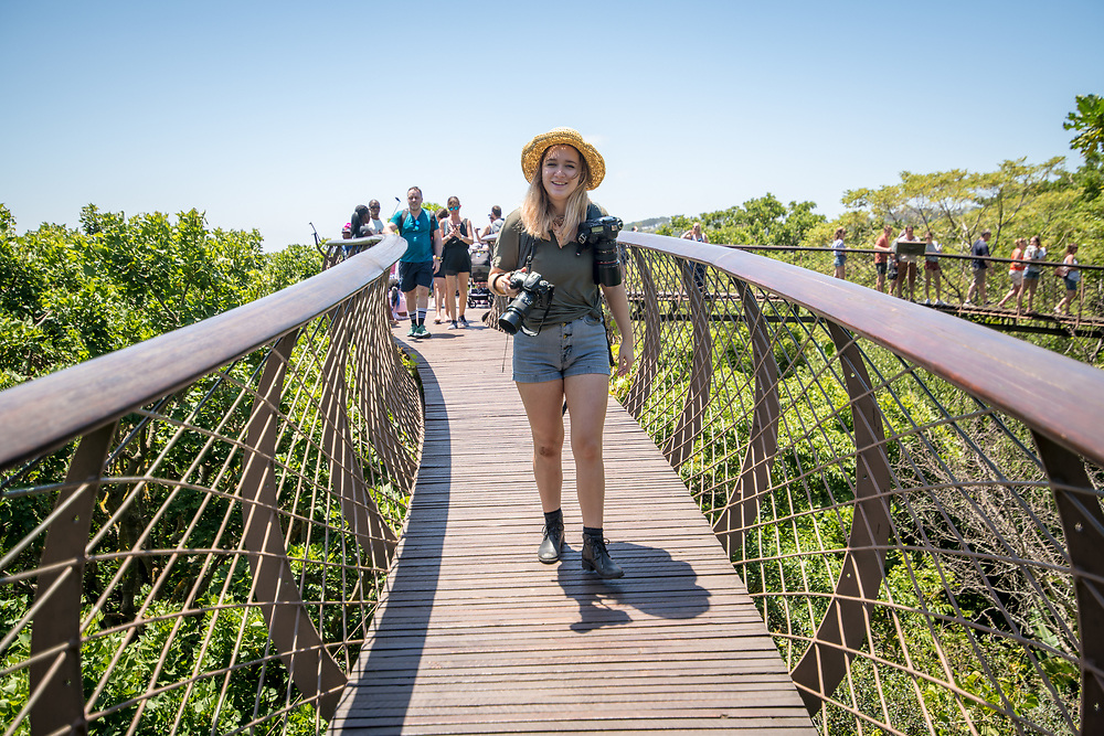 Young female photographer walking along The Centenary Tree Canopy Walkway at the Kirstenbosch Botanical Gardens in Cape Town, South Africa