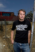 Los Angeles, California: artist Shepard Fairey on the street in front of his studio, with the Obama billboard he designed in the backdrop, on Sunset Blvd. around the corner from Dodger Stadium in the Echo Park district of Los Angeles, 7/14/08.