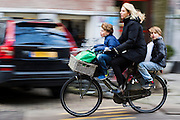 In Amsterdam fietst een vrouw met een kind voorop en een kind achterop door de stad.<br /> <br /> In Amsterdam a woman cycles with a child at the front and one child at the back of the bike.