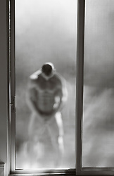naked man outdoors in front of a sliding door