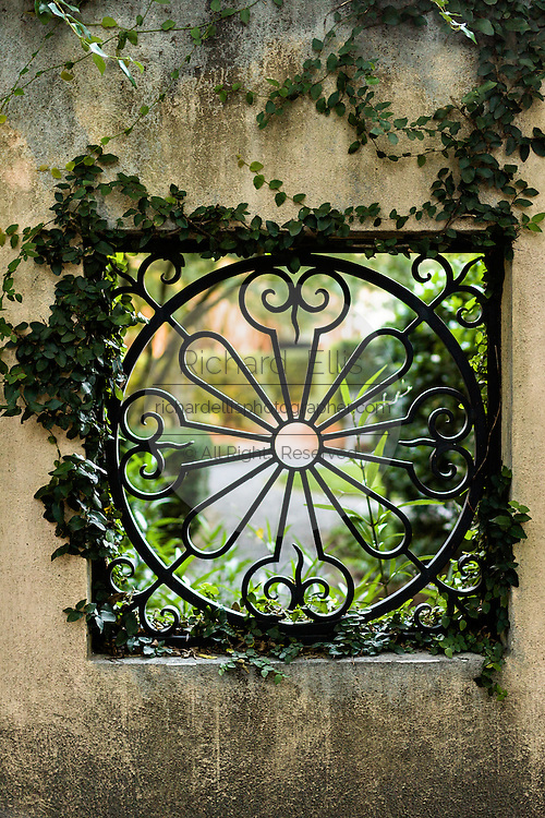 Decorative ironwork window in a wall at Middleton-Pinckney House headquarters of the Spoleto Festival USA in historic Charleston, SC.