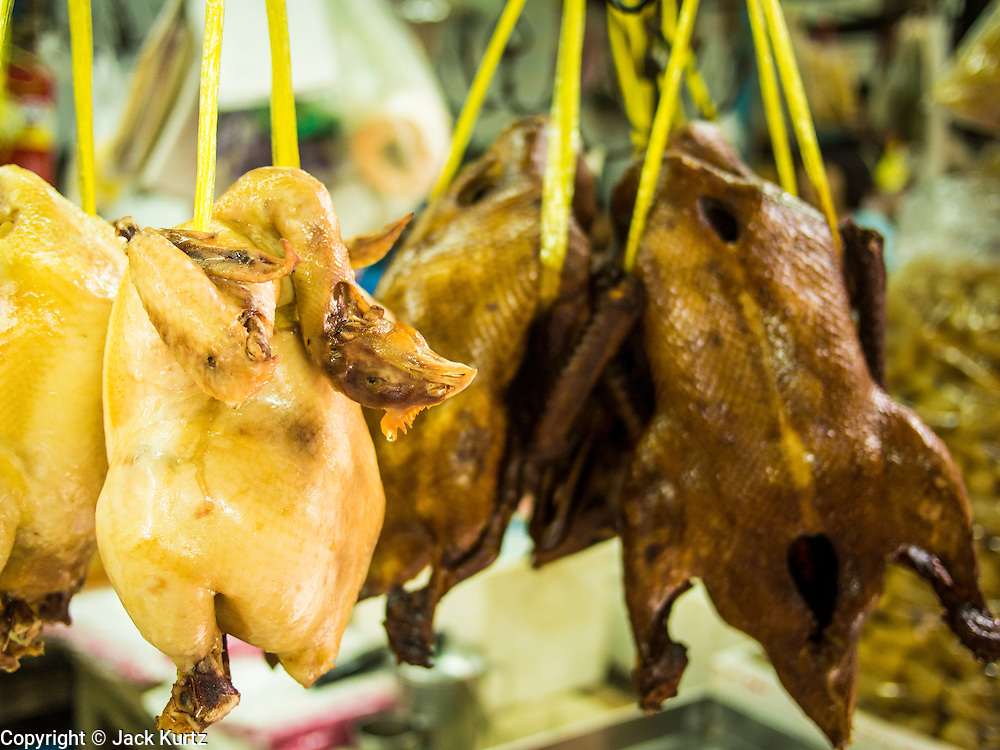 11 SEPTEMBER 2013 - BANGKOK, THAILAND:  Fresh cooked chickens hang in food stall window in the Chinatown section of Bangkok. Thailand in general, and Bangkok in particular, has a vibrant tradition of street food and eating on the run. In recent years, Bangkok's street food has become something of an international landmark and is being written about in glossy travel magazines and in the pages of the New York Times.        PHOTO BY JACK KURTZ