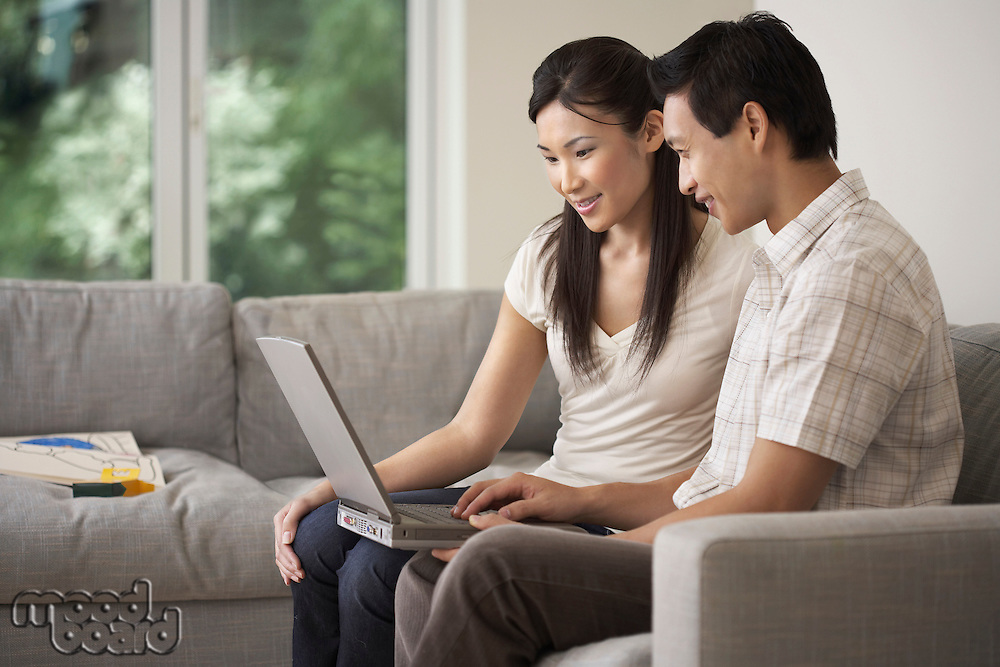 Couple sitting side by side on Sofa Using a Laptop