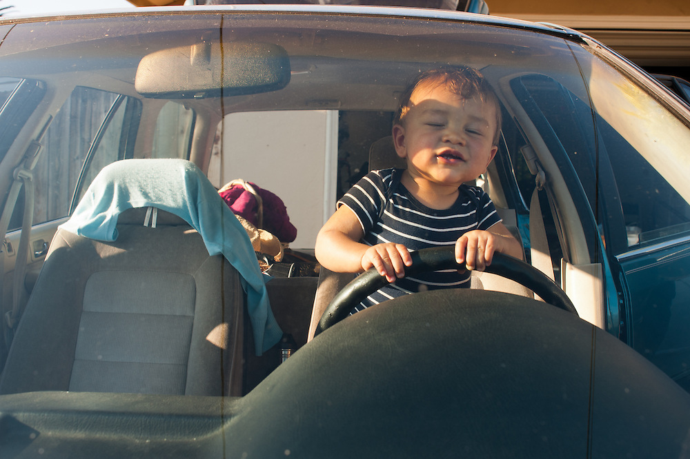 little boy relishing his turn behind the steering wheel of a car, standing on the frontseat